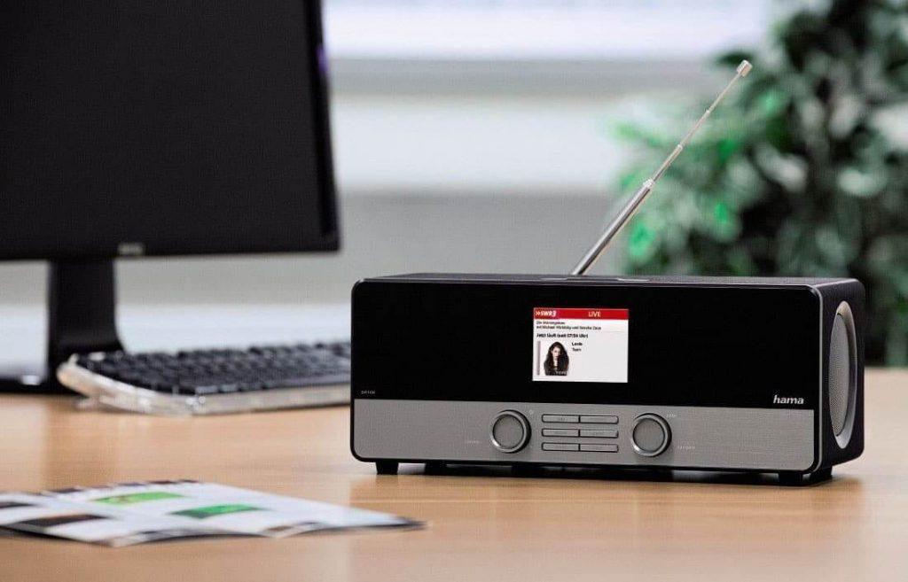 Hama DIR3100 auf Schreibtisch mit Antenne und Coverbild auf Display